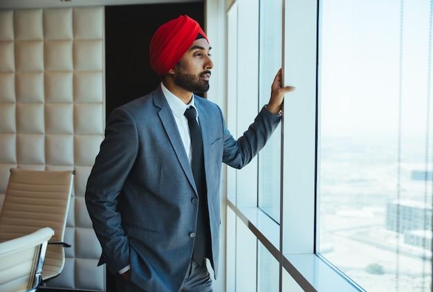 Индийский бизнесмен, глядя в окно в своем кабинете