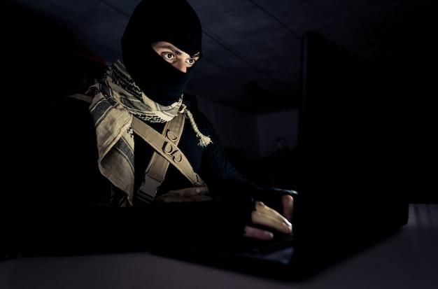 彼のコンピューターで作業するテロリスト