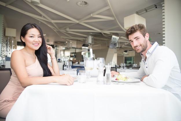 高級レストランでロマンチックなランチを持っている若いカップル
