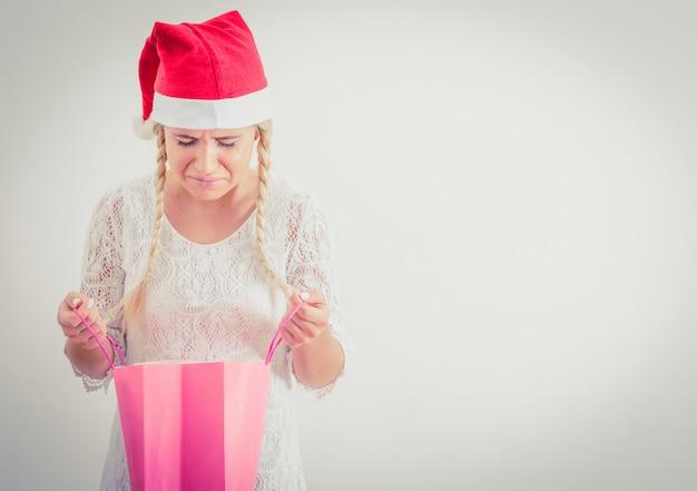 Женщина в шляпе санта, открытие рождественского подарка