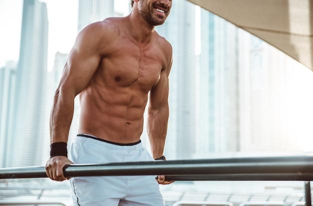 バーでの演習を行う上半身裸の男