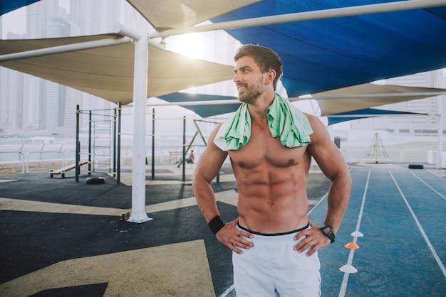上半身裸の男がエクササイズと屋外のさまざまな演習を行う