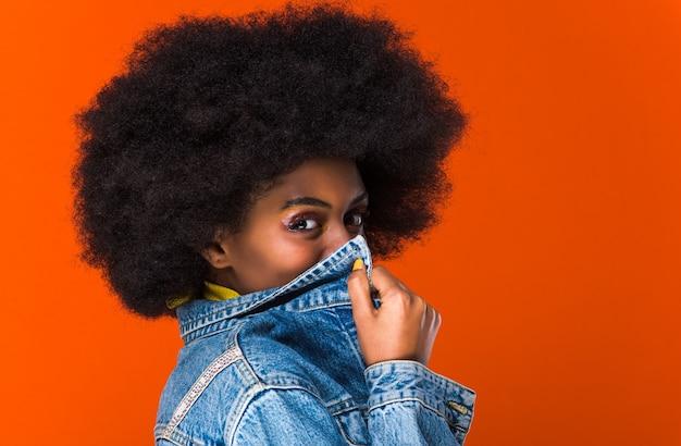 ジャケットで口を覆っている美しいアフリカ人