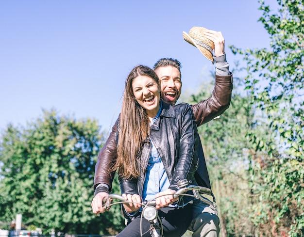 Пара катается на велосипеде и смеется