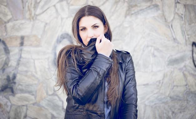 彼女の口を覆っている革のジャケットの女性