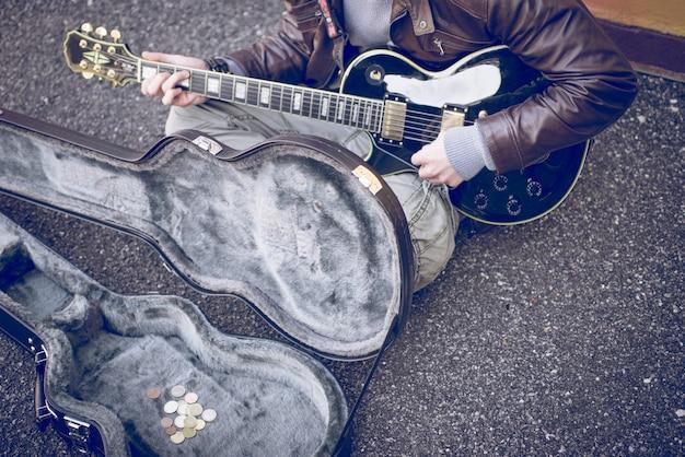 Уличный музыкант играет на гитаре на земле