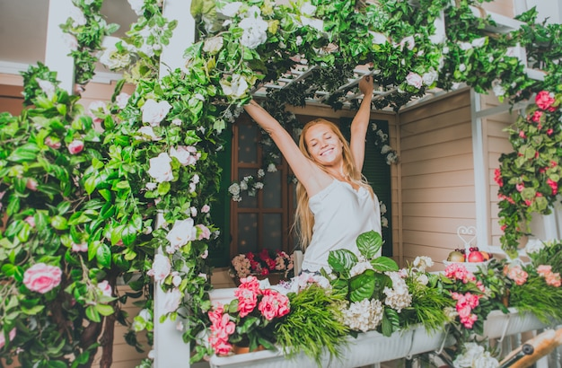 彼女の美しい花の家の前に滞在する若い女性