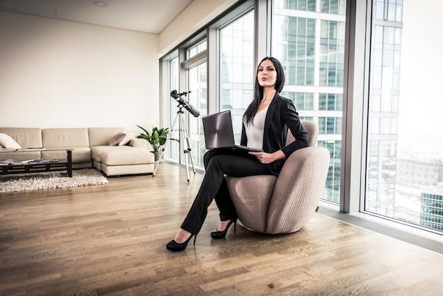 ビジネスの女性が彼女のアパートでポーズ