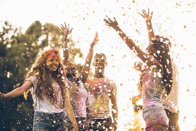 Группа подростков, играющих с цветами на фестивале холи, в парке