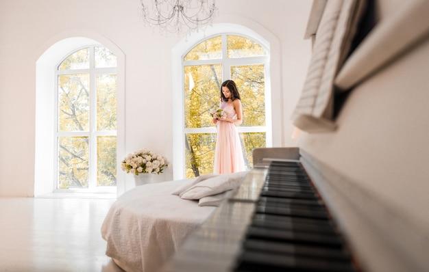 Красивая женщина с модным свадебным платьем готовится к событию