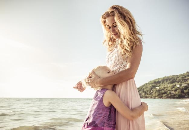 ママと娘はビーチでハグ