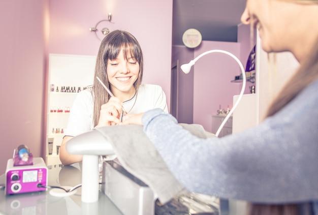 美容サロンで爪の治療を行う女性