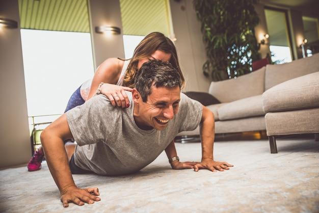 Пара делает метки фитнеса в гостиной дома