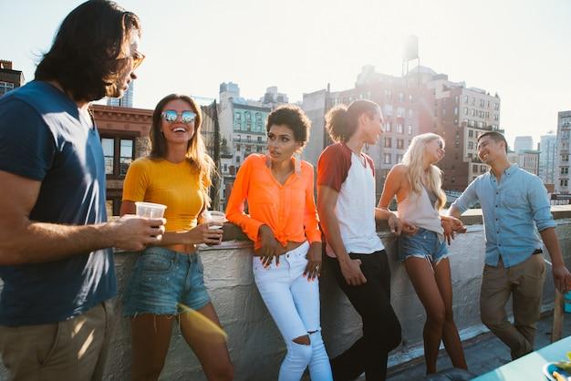 ニューヨーク市の屋上で一緒に時間を過ごしている友人のグループ、幸せな人々とライフスタイルのコンセプト
