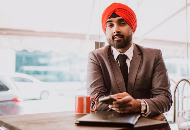 コーヒーを取るカフェでインドのビジネスマン