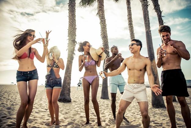 ビーチで大きなパーティーを作る友人のグループ