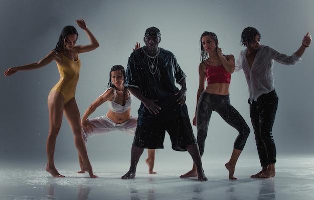 雨の影響でステージ上で踊るダンサーのグループ