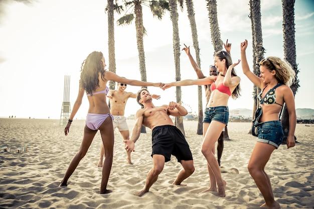 ビーチで大きなパーティーやゲームを作る友人のグループ