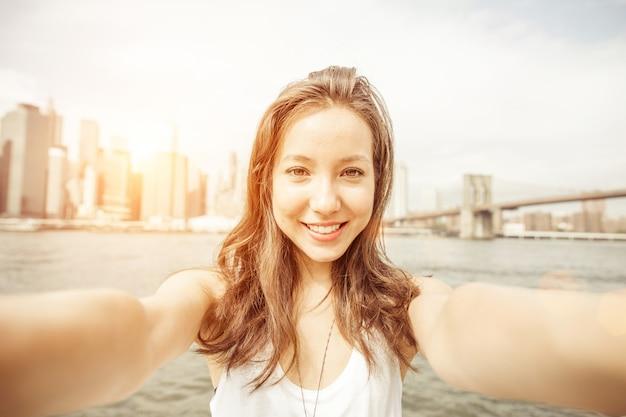カメラを押しながらニューヨークでセルフポートレートを取る美しいアジアの少女