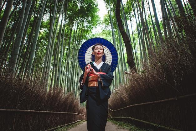 竹の森を歩く美しい日本の年配の女性
