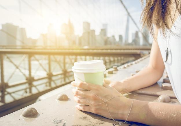 ニューヨークのブルックリン橋にコーヒーの紙コップを保持している女性にクローズアップ