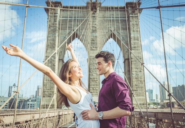 有名なブルックリン橋でお互いをハグ幸せなカップル