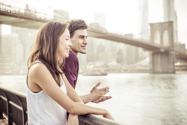 有名なブルックリン橋の前で話している幸せなカップル