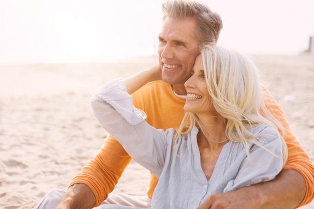 ビーチで過ごす幸せな先輩カップル。愛、老後、人についての概念