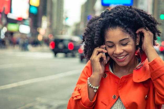 ニューヨークのタイムスクエアで電話をかけるアメリカ人女性。アーバンライフスタイルのコンセプト