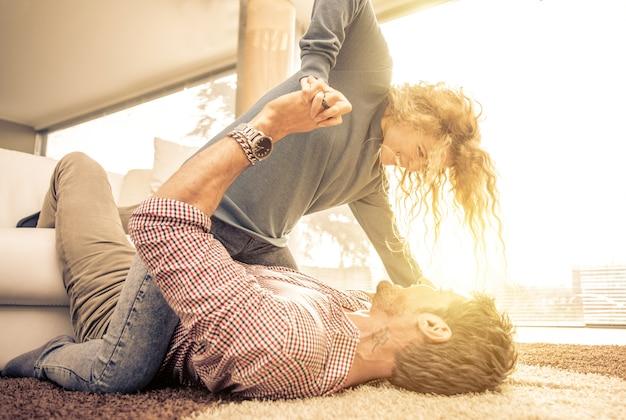 Молодая пара играет на ковре для удовольствия