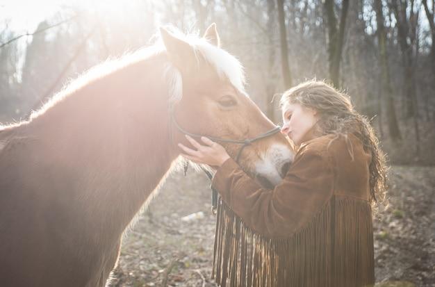 Женщина целует лошадь