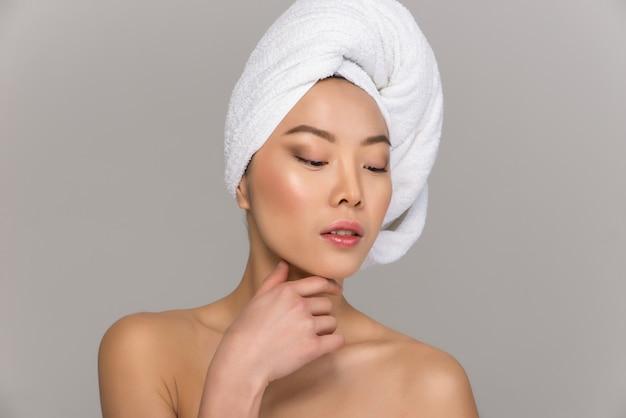 美しいアジアの女性の美しさの肖像画。鏡の前に立って彼女の顔の世話をしている中国の女の子。美容スタジオショット