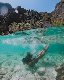 Небольшая лагуна в эль нидо. женщина, наслаждаясь время в кристально прозрачной воде, с тропическими джунглями. понятие о путешествии и природе