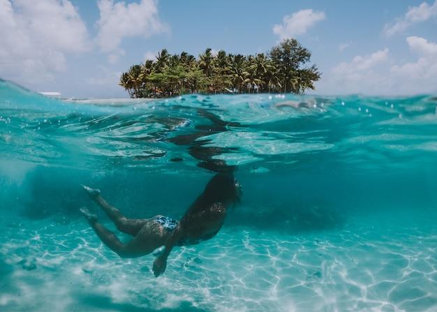 Женщина плавая под водой с тропическим ландшафтом. понятие об отдыхе и природе. снято с помощью подводной камеры