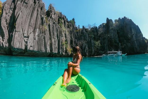 美しい女性は、フィリピンのコロンのラグーンで時間をお楽しみください。熱帯の放浪旅行のコンセプト