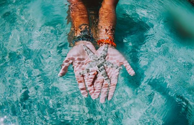 Женщина плавает под водой. понятие об отдыхе и природе. показываю морскую звезду в ее руках
