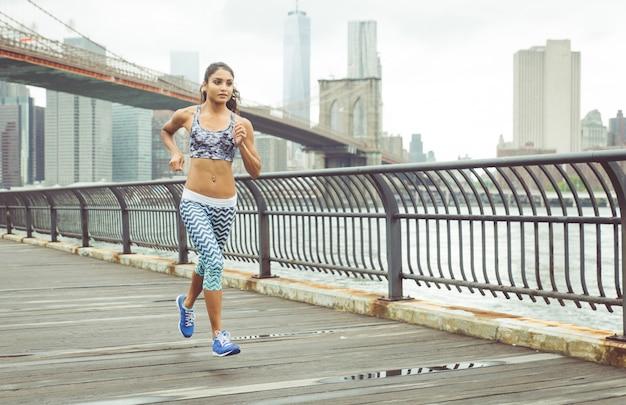 バックグラウンドでニューヨークのスカイラインと桟橋で走っている少女