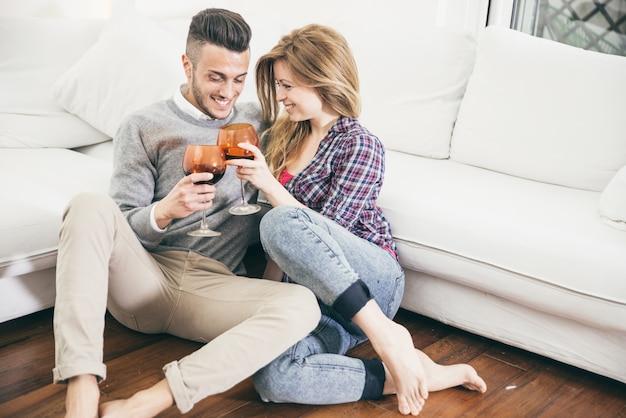 若いカップルがリビングルームでワインを飲む