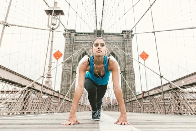 実行する前に早朝にストレッチを作る美しい少女。ブルックリンブリッジとバックグラウンドでニューヨークのスカイライン