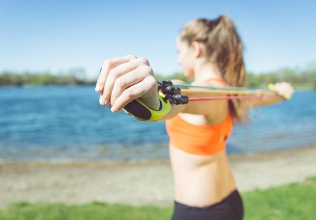 重みでトレーニングの女性。自然の中で屋外トレーニングについての概念