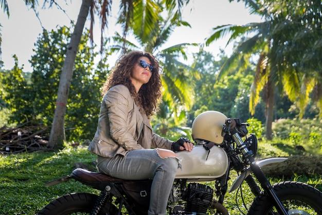 Женский байкер за рулем мотоцикла кафе гонщик