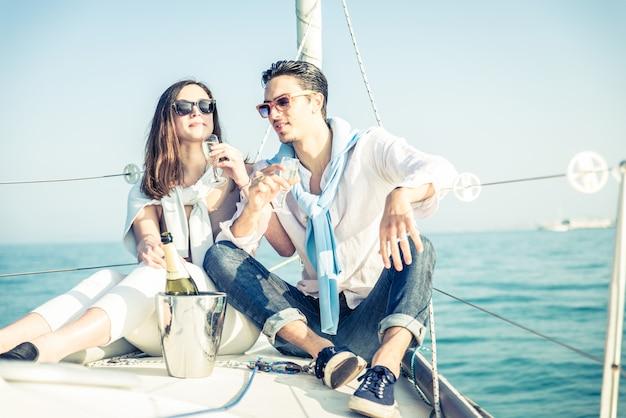 カップルはボートに乗ってシャンパンを飲む