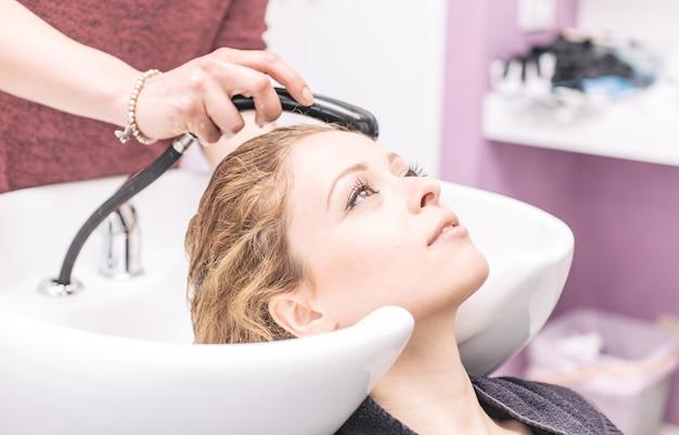 女性は、美容院でシャンプーを作る