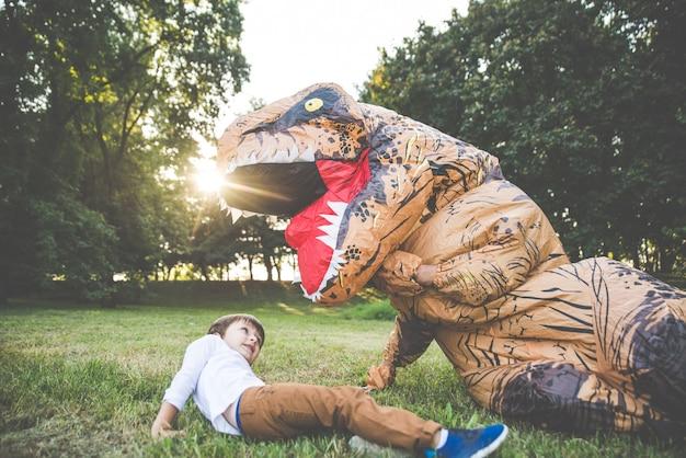父と息子が公園で遊んで、恐竜の衣装を着て、屋外の家族と楽しんで