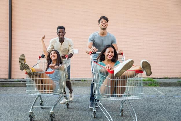 ショッピングカートで実行している若い幸せなお友達