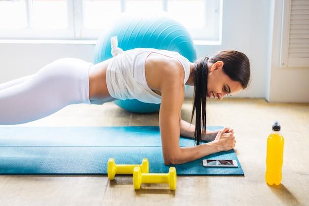 陽気な女性が自宅でトレーニング