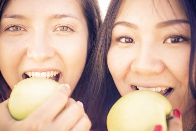 Пара девушек кусает зеленые яблоки
