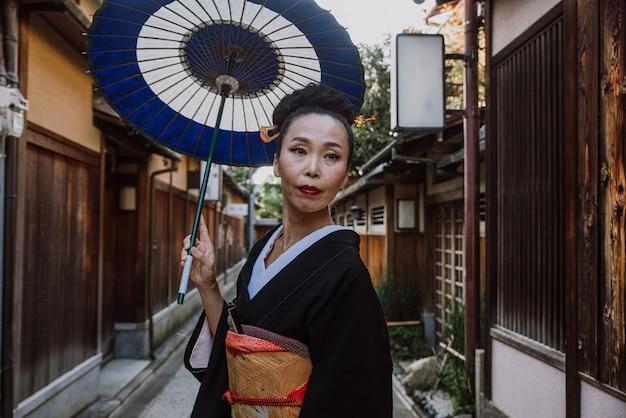村を歩いている美しい日本の年配の女性。典型的な日本の伝統的なライフスタイル