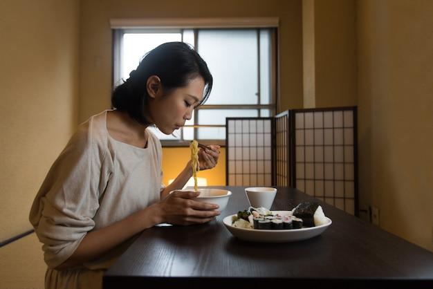 Японка ест в традиционной квартире