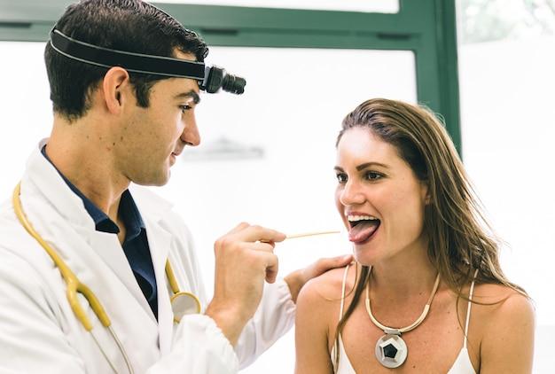 医師が医療スティックで女性の喉をチェック